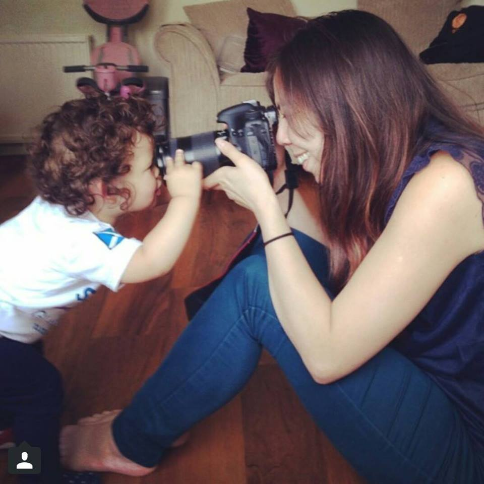 Image of Jo Foo taking photos of an inquisitive toddler
