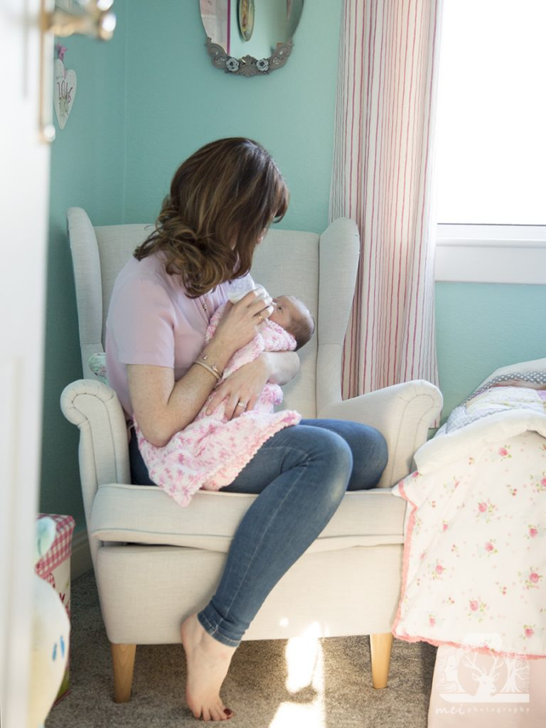 A photo of mother and daughter taken through a doorway. They are sitting on a chair together and the baby is being bottle fed.