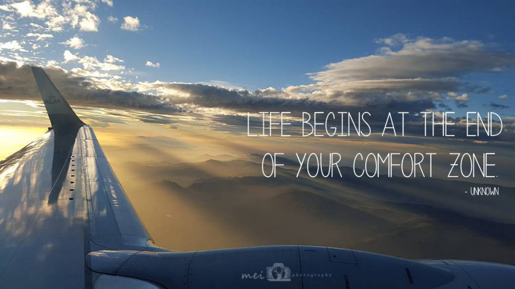 "Image of a sunrise out of a plane window with ""Life Begins at the End of Your Comfort Zone"" quote"