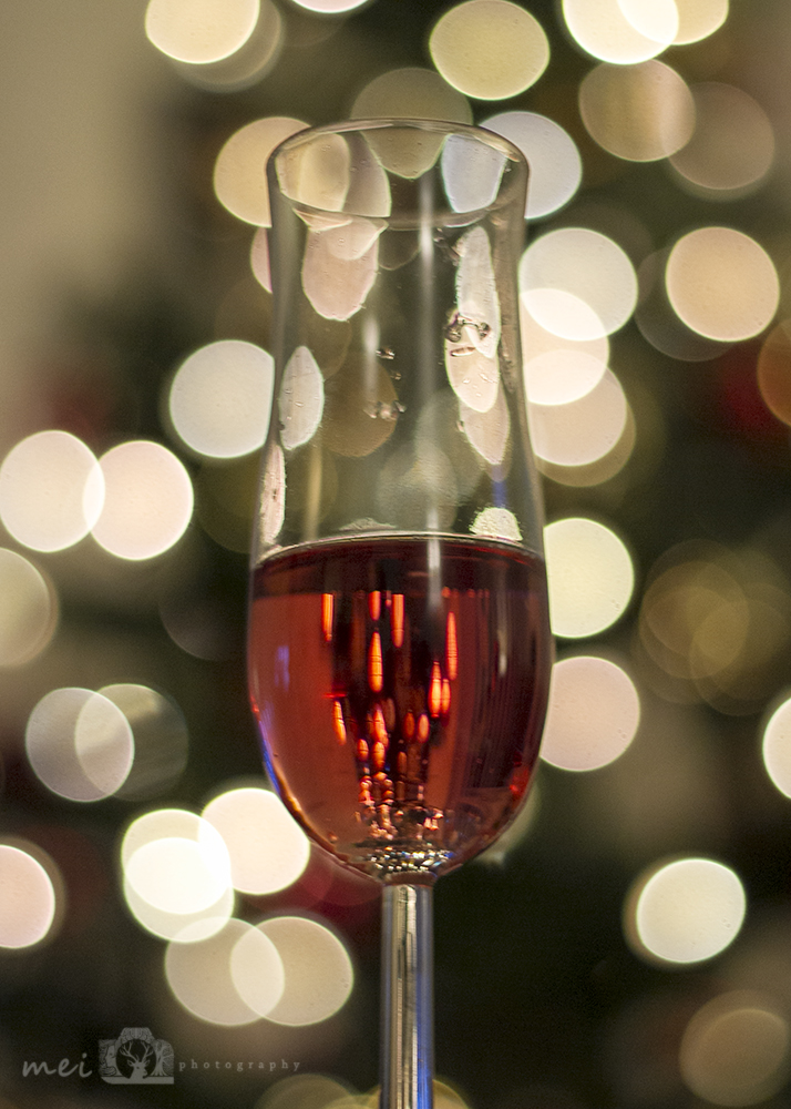 A champagne glass with rose wine and a christmas tree in the background. The christmas tree is out of focus so the fairy lights show as large round circles of light (bokeh).
