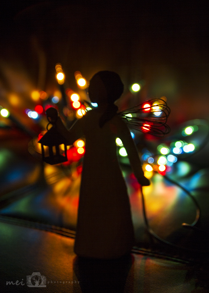 A silhouette of a fairy ornament with coloured lights out-of-focus behind it on a dark background.