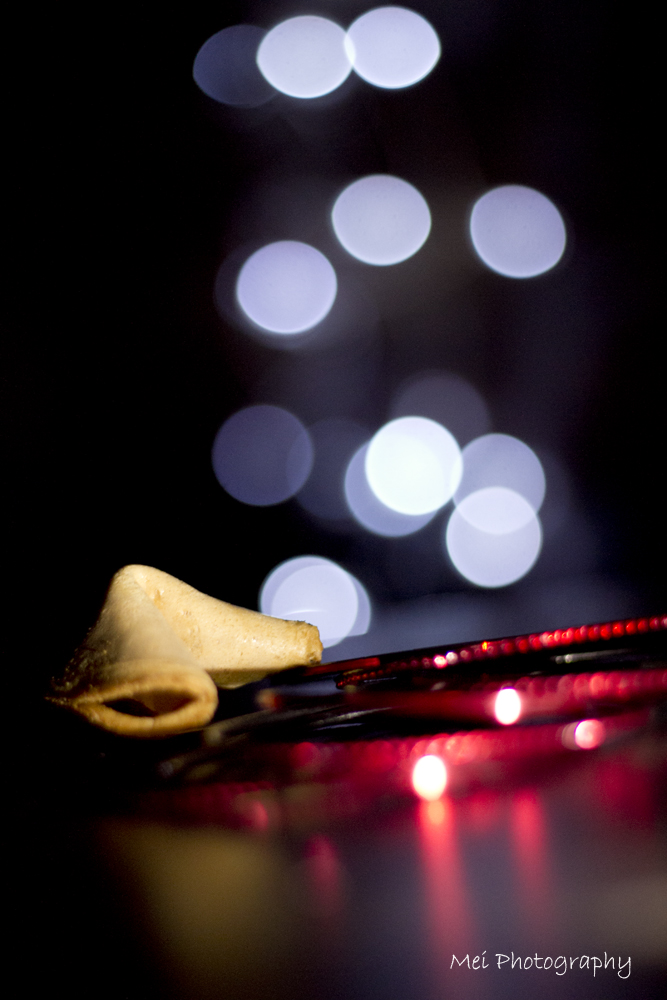 Abstract image of a fortune cookie, red bracelets and out of focus fairy lights (bokeh) in the background to celebrate Chinese New Year.