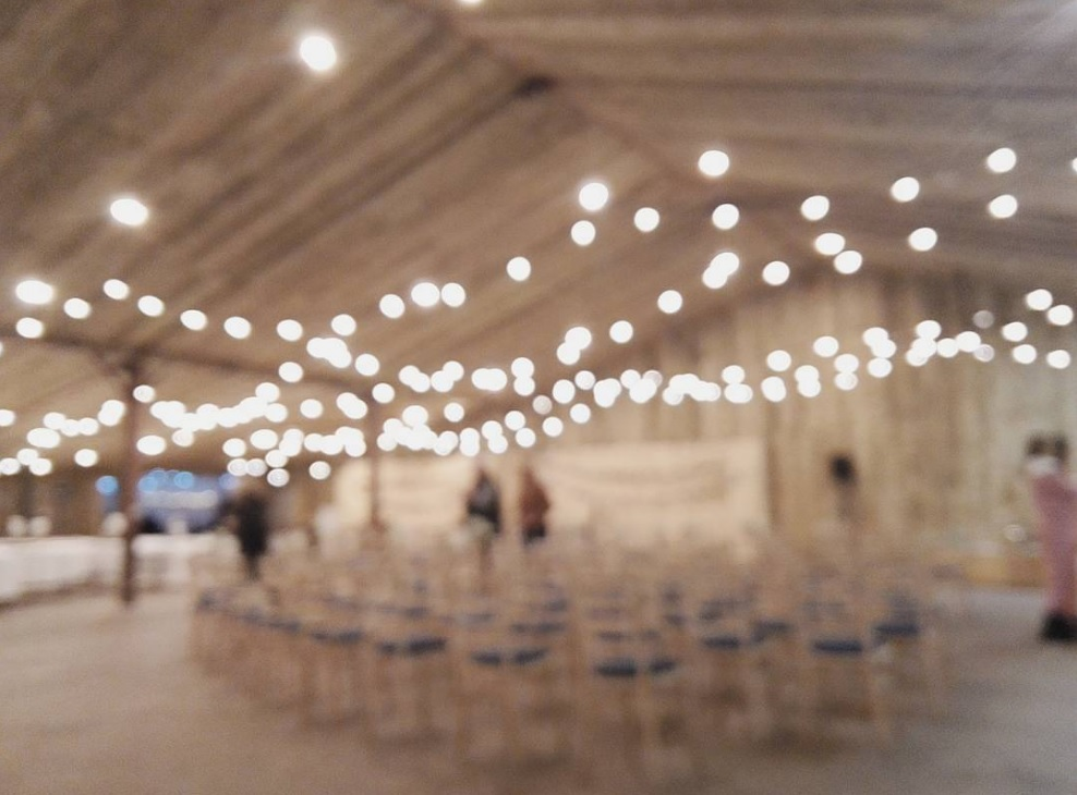 A bright image of a barn wedding with chairs and people and the fairy lights out of focus to get bright warm white circles of light across the image.