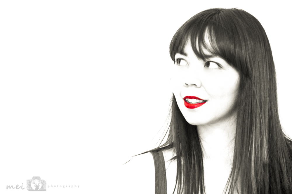 a photo of a woman in black and white on a bright white background. she is wearing red lipstick - this is the only part in colour