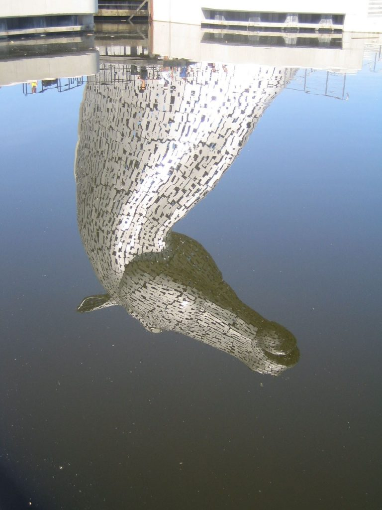 Metal horse reflecting in blue water (kelpie from Scotland)