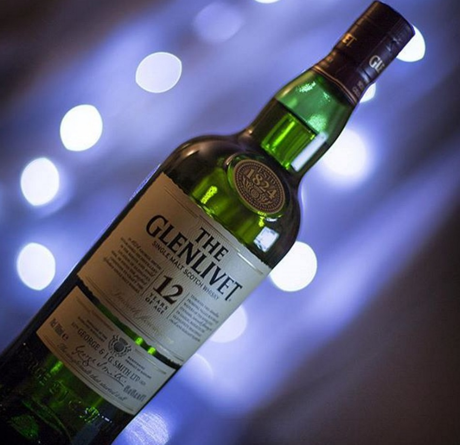 A bottle of Glenlivet whisky (green with cream label) and a blue tinted background with fairy lights out of focus (bokeh)